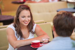 Young man and woman drinking coffee outdoor and having a chat on royalty free stock photography