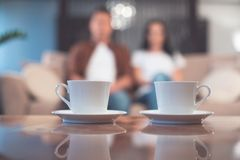 Young man and woman drinking hot beverage at home. Low angle focus on white cups of tea on small plates on desk. Married couple is relaxing on sofa on background Stock Images