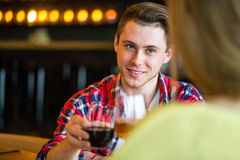 Young man and woman drinking wine in a restaurant. Young man and woman drinking wine on a date. man and woman on a date. Burger concept Royalty Free Stock Image