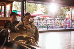 Young man and woman driving bumper car at fairground Royalty Free Stock Images