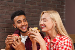 Young Man And Woman Eating Fast Food Burgers Sitting At Wooden Table In Cafe Royalty Free Stock Photo