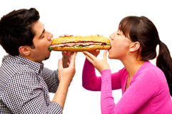 Young man and a woman eating sandwich from. Two sides isolated on white Royalty Free Stock Photography