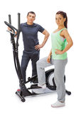 Young man and woman with elliptical cross trainer. Stock Image
