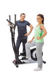 Young man and woman with elliptical cross trainer. Royalty Free Stock Image
