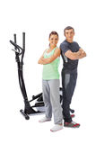Young man and woman with elliptical cross trainer. Royalty Free Stock Photos