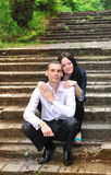 Young man and woman embracing in park sitting on background of  old staircase. Stock Images