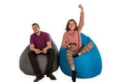 Young man and woman are enthusiastic about playing video games w. Young men and women are enthusiastic about playing video games while sitting on blue and grey Royalty Free Stock Images
