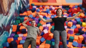Young man and woman is falling back to soft cubes in a sports hall stock footage