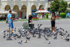 Young man and woman are feeding pigeons in the square of Aristot Royalty Free Stock Photography