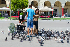 Young man and woman are feeding pigeons in square of Aristotle i Royalty Free Stock Images