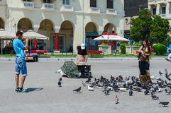 Young man and woman are feeding pigeons on square of Aristotle i Royalty Free Stock Photos