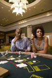 Young man and woman gambling at poker table, portrait Stock Photos