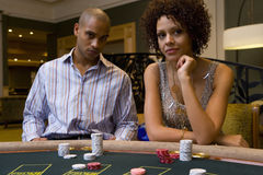 Young man and woman gambling at poker table, portrait Stock Images