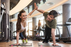 Young man and woman giving high five from basic plank pose durin. Young fit men and women smiling and looking at camera while giving high five from basic plank Stock Image