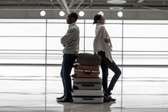 Young man and woman going to travel with luggage. Happy journey. Full length profile of young romantic couple is leaning on suitcases at airport hall. They are Royalty Free Stock Images