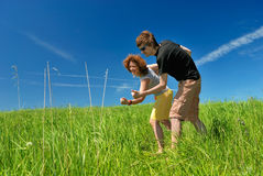 Young man and woman on green field Royalty Free Stock Images