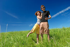 Young man and woman on green field Royalty Free Stock Image