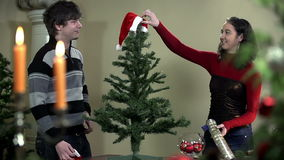 Young man and woman hanging a Santa hat on Christmas Tree stock footage