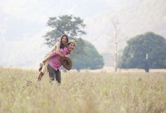 Young man and woman with happy emotion playing on field Royalty Free Stock Photos