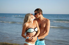 Young man and woman have a rest at the sea kissing Royalty Free Stock Photos