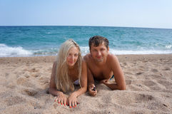 Young man and woman have a rest at the sea Stock Photography