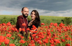 Young man and woman having date in the field of poppies stock photo