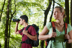 Young man and woman hiking with binoculars. Young people trekking among trees and looking at birds with binoculars. Horizontal shape, side view, waist up Royalty Free Stock Photo