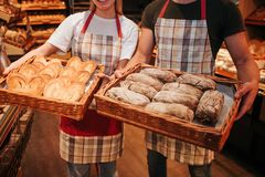 Young man and woman hold baskets of fresh tasty white dark bread in hands. Stand in grocery store. Cut view. Busy. Workers royalty free stock images