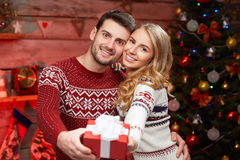 Young man and woman holding a wrapped gift Stock Photography