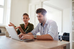 Young man and woman at home using laptop Royalty Free Stock Image