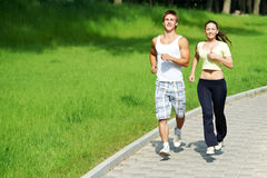 Young man and woman jogging. Young fitness couple of man and woman doing jogging sport outdoors Stock Photo
