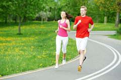 Young man and woman jogging outdoors. Young fitness men and women doing jogging sport outdoors Stock Photos