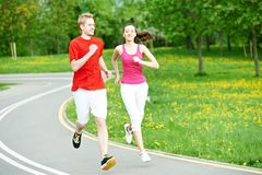 Young man and woman jogging outdoors. Young fitness men and women doing jogging run sport outdoors Royalty Free Stock Images