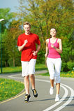 Young man and woman jogging outdoors Stock Images