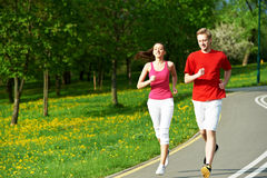 Young man and woman jogging outdoors. Young fitness men and women doing jogging run sport outdoors Royalty Free Stock Photo