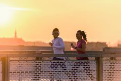 Young man and woman jogging together over bridge in the sunset or sunrise royalty free stock photo