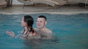 Young man and woman joking and smiling in the pool. stock video