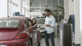 Young man and woman just bought a car in car showroom. Happy swarthy guy looks on girl in car and smiling. Pretty girl appears from car`s window and demonstrate stock footage