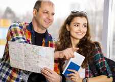 Young man and woman. Keep a map and shows the direction. Europeans. Gathered in a guided tour. Close-up. Honeymoon. Young men and woman. Keep a map and shows the Royalty Free Stock Image