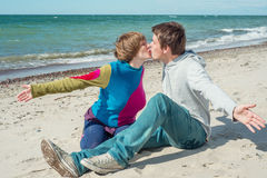 Young man and woman kissing on the beach. Cheerful women and men kissing on the beach Stock Photos