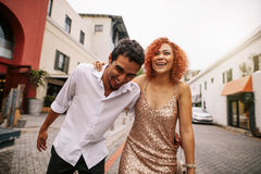 Young man and woman laughing while walking on street. royalty free stock photography