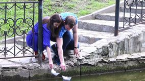 Young man and woman are launched paper boats in park. At summer day stock video footage