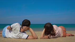 Young man and woman laying on a beautiful beach watch a landing airplane stock video