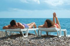 Young man and woman lies in chaise lounge. On beach Royalty Free Stock Images