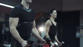 Young man and woman lifting weights in a gym stock video