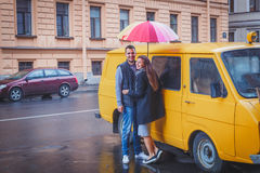 Young man and woman with long hair hugging under a bright colored umbrella smiling against the background of yellow van Royalty Free Stock Image