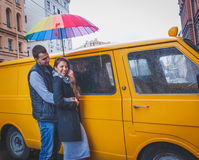 Young man and woman with long hair hugging under a bright colored umbrella  smiling against the background of yellow van Stock Image