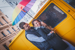 Young man and woman with long hair hugging under a bright colored umbrella smiling against the background of yellow van Stock Photography