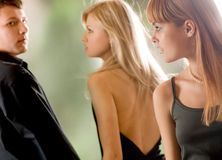 Young man and woman looking against each other and the jealous g Stock Photography
