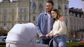 Young man and woman looking at baby swinging carriage, family love, hugging. Stock footage stock video